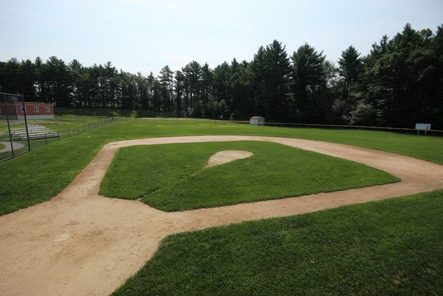 Image of tree lined baseball field, with dugout and out building