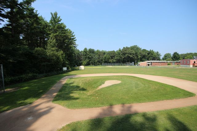Side view of Fuller Meadow baseball field with building in back right corner