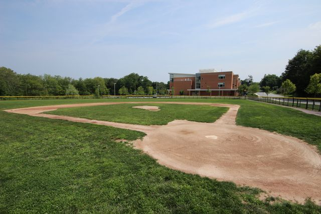 Baseball field with two story brick building in background