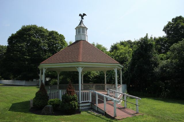 Gazebo in grassy lawn with forest in background
