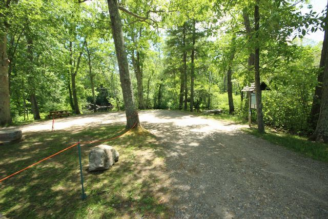 Gravel driveway leading to landing informational board, surrounded by trees