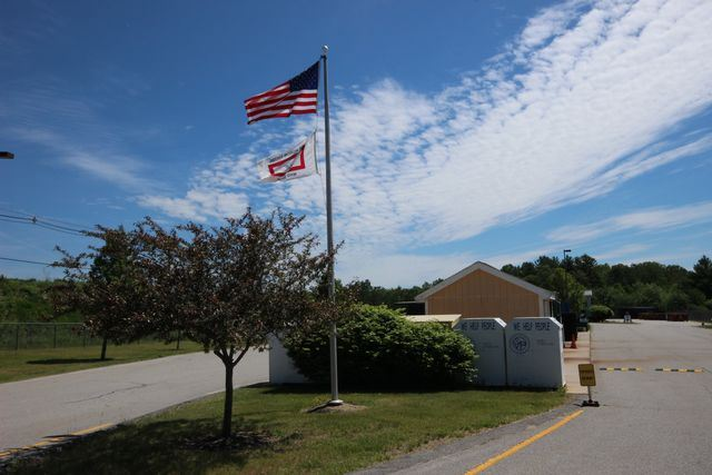 American flag at entrance to transfer station with outbuilding
